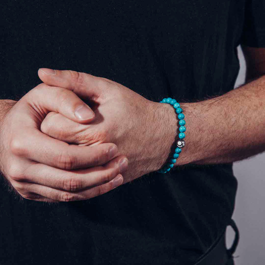 Male wearing turquoise stone bracelet on wrist with hands clasped together.