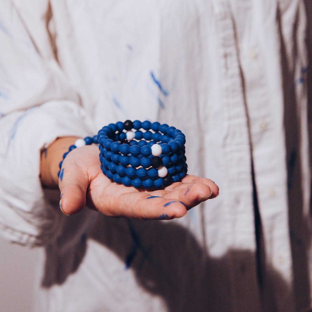 Female in white shirt with blue paint stains holding a stack of classic blue silicone beaded bracelets.