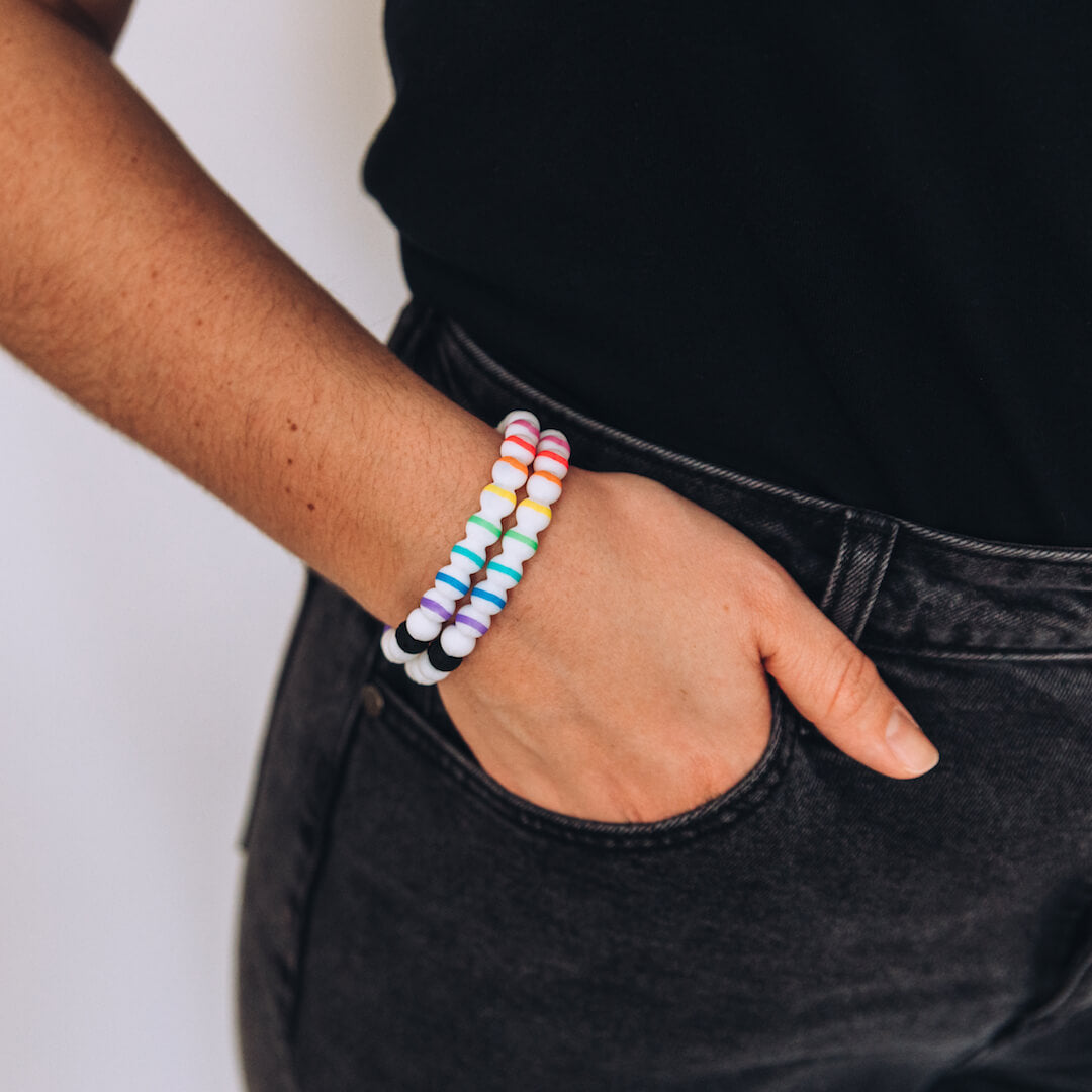 Woman wearing two silicone beaded bracelets with rainbow stripes with hand in pocket.