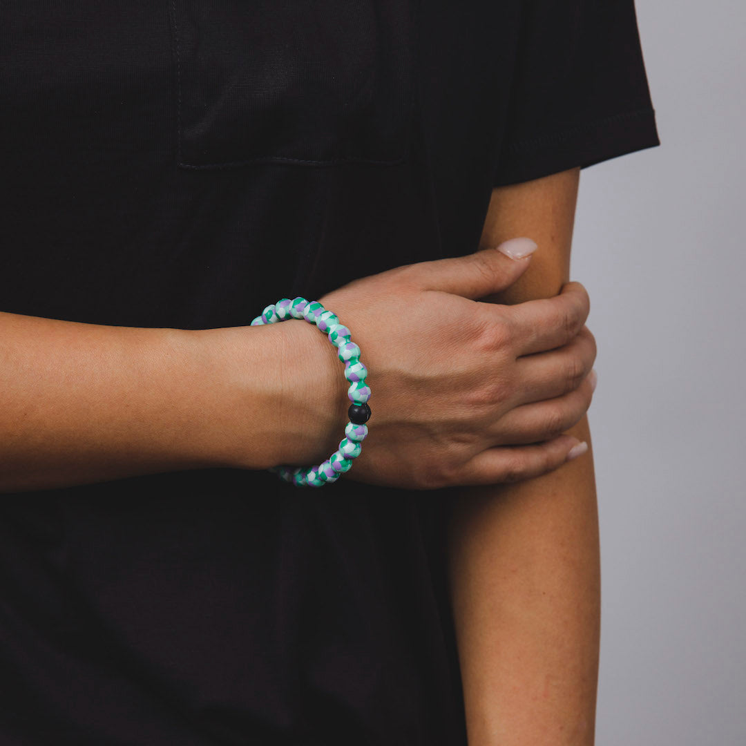 Woman wearing silicone beaded bracelet with mermaid scales pattern on wrist