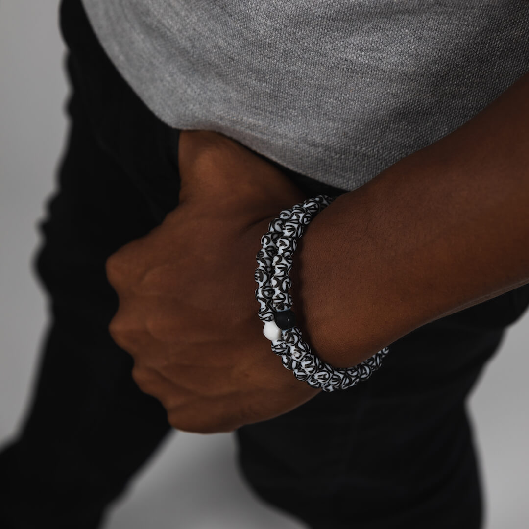 Male wearing two silicone beaded bracelets with Avenger's A logo pattern on wrist.