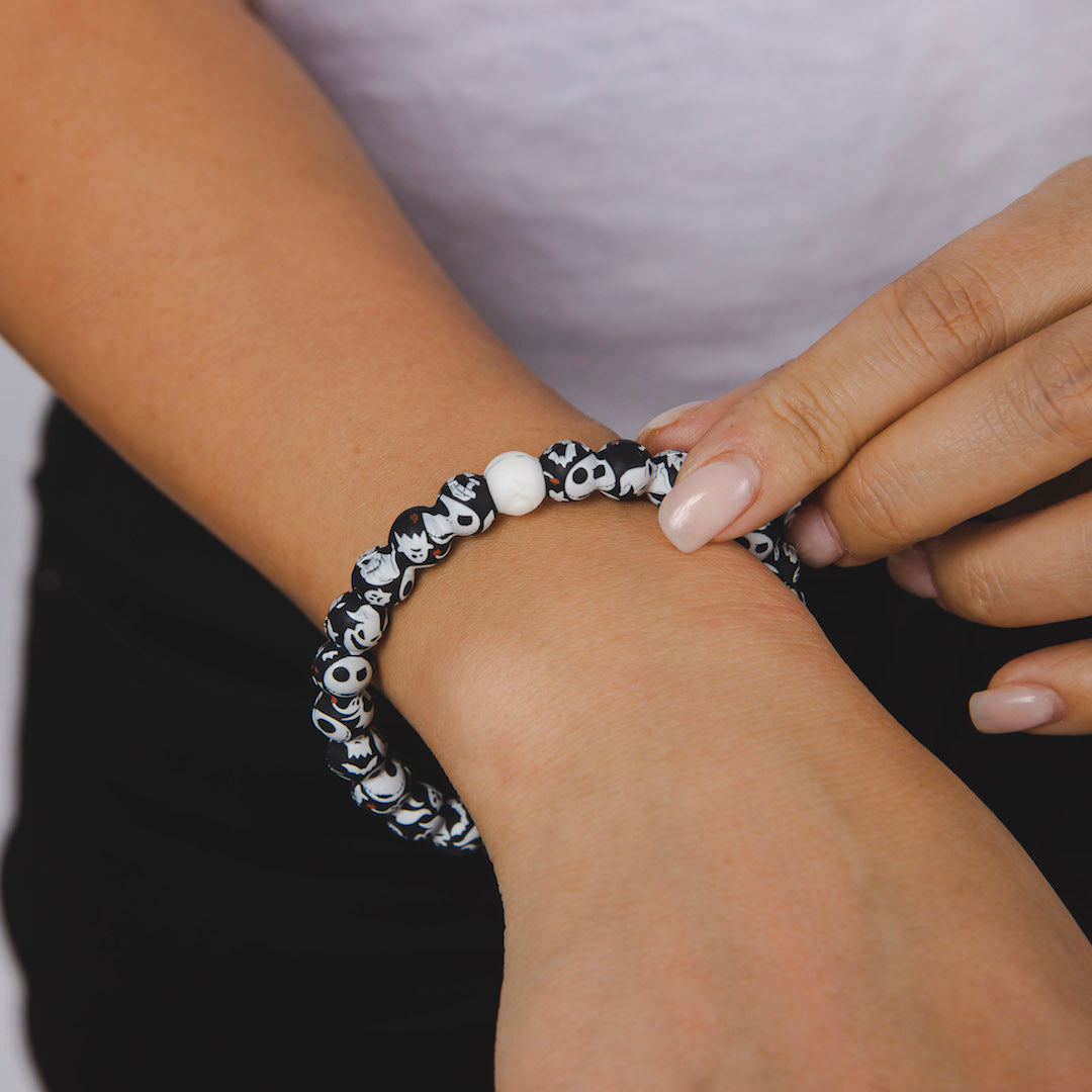 Woman wearing a silicone beaded bracelet with skeleton pattern on wrist