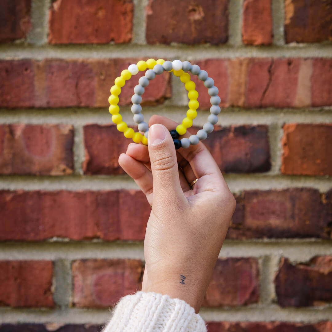 Person holding two yellow and gray split silicone beaded bracelets on wrist.