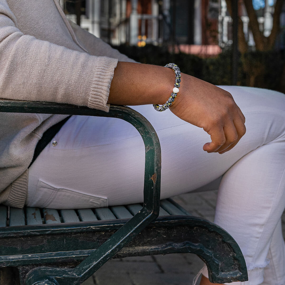 Woman sitting on bench wearing a silicone beaded bracelet with