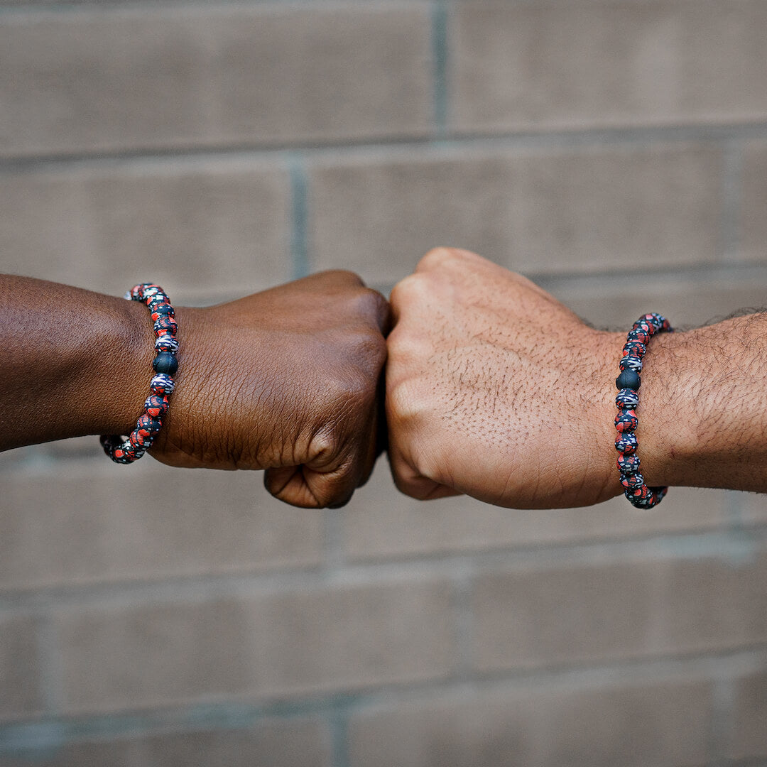 Two people wearing silicone beaded bracelets with Muhammad Ali patterns on wrist.