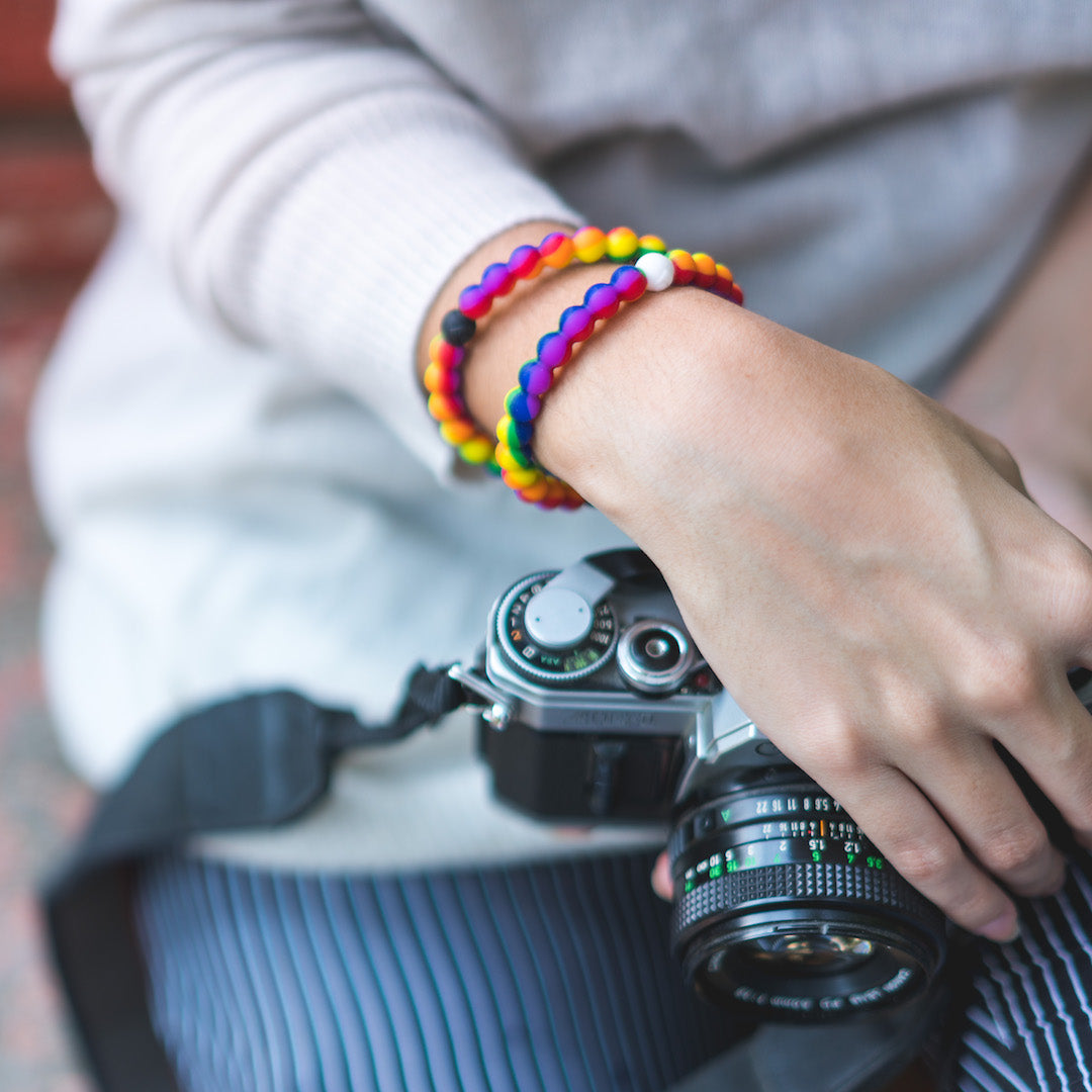 Woman holding camera in lap with rainbow silicone beaded bracelets on wrist.