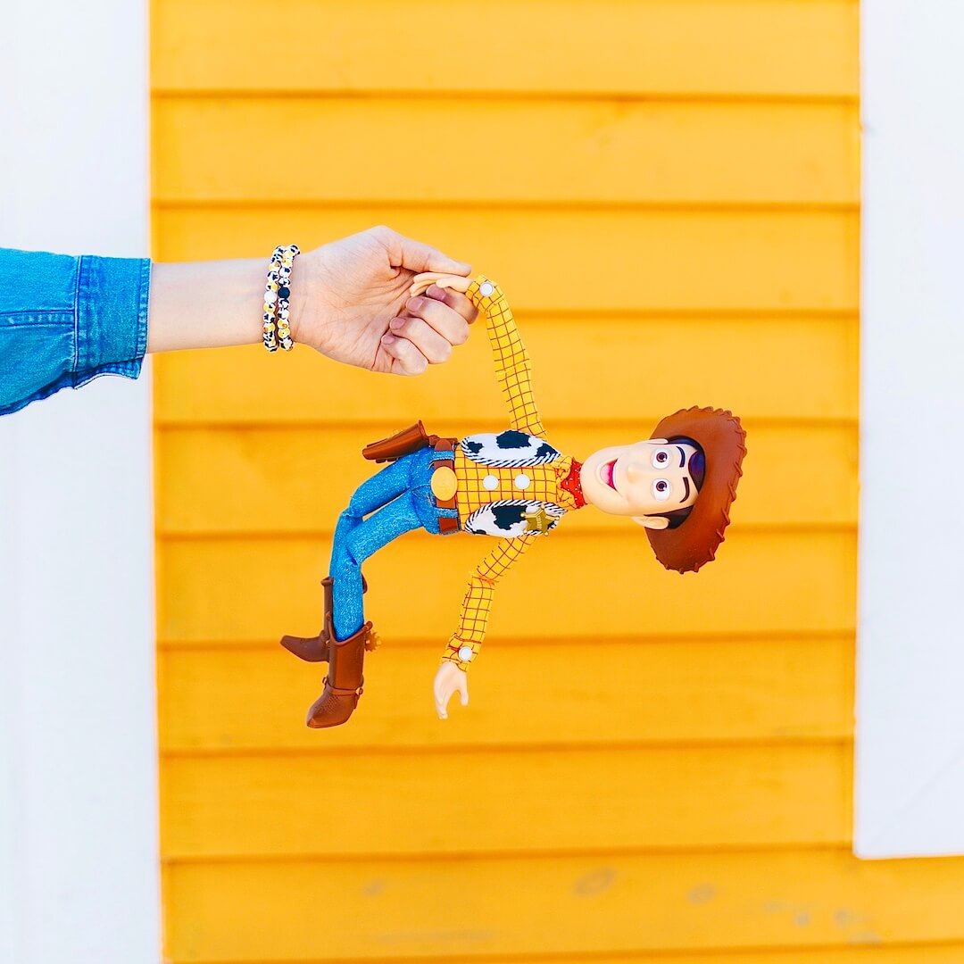Woman wearing silicone beaded bracelet with Sheriff Woody pattern on wrist holding Sheriff Woody toy