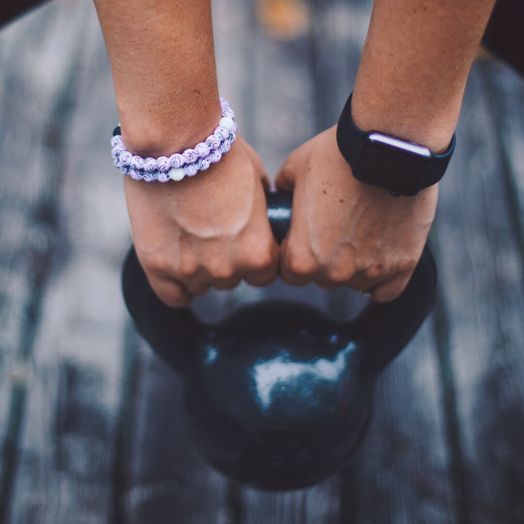 Woman holding dumbell with light purple silicone beaded bracelet with workout equipment icons on wrist.