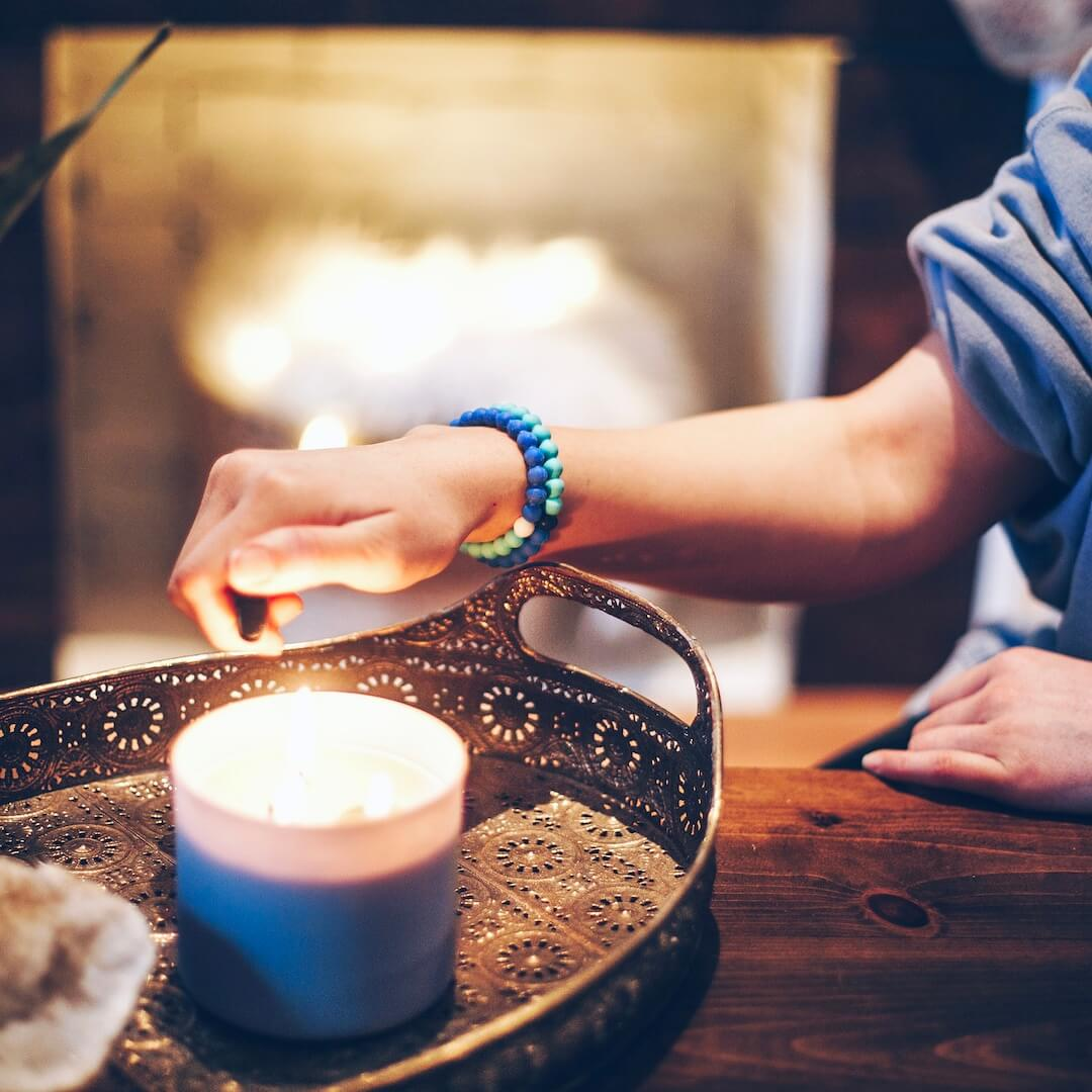 Woman lighting a candle by the fireplace wearing a split light blue and dark blue silicone beaded bracelet on wrist.
