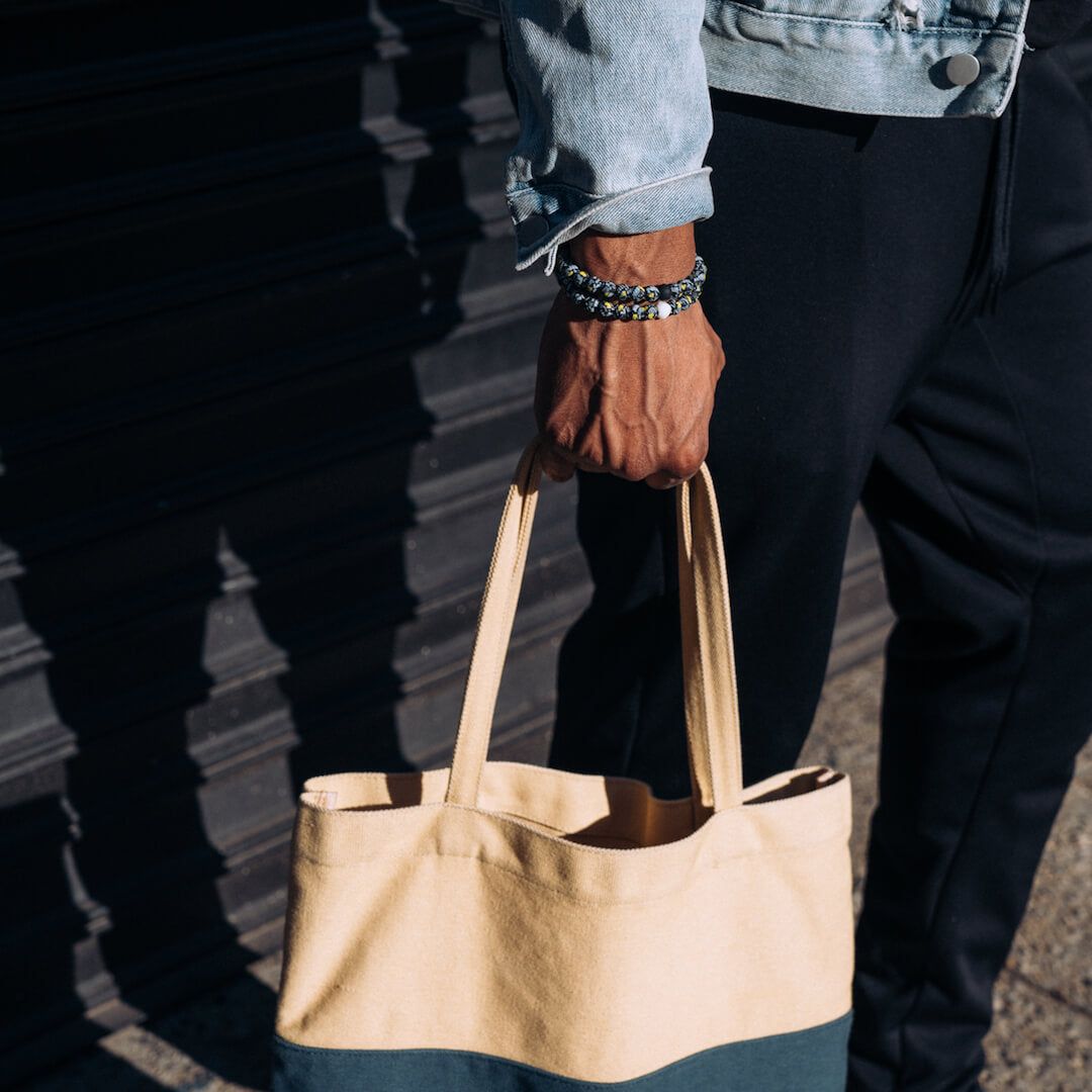 Man holding tote bag wearing a silicone beaded bracelet with