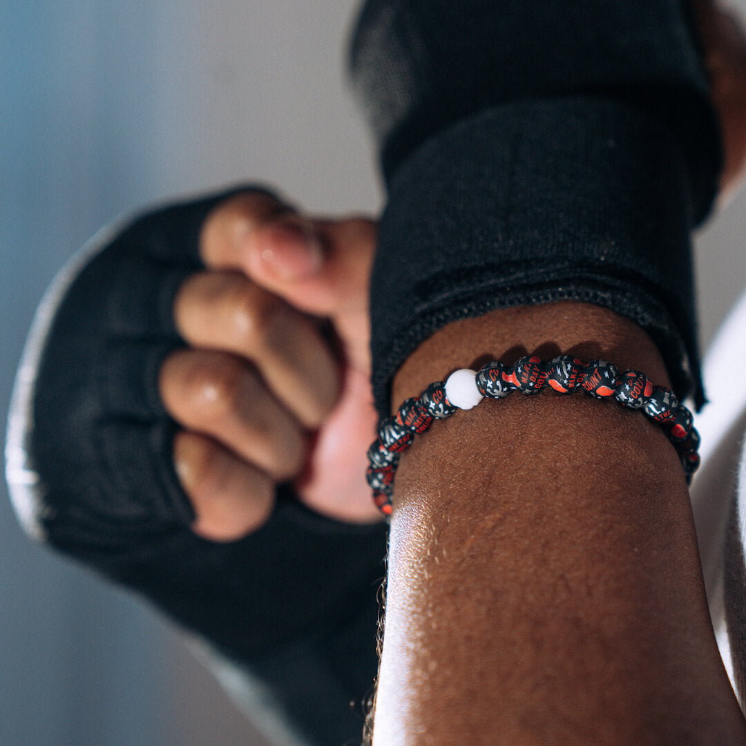 Person wearing boxing gloves with a silicone beaded bracelet with Muhammad Ali pattern on wrist.