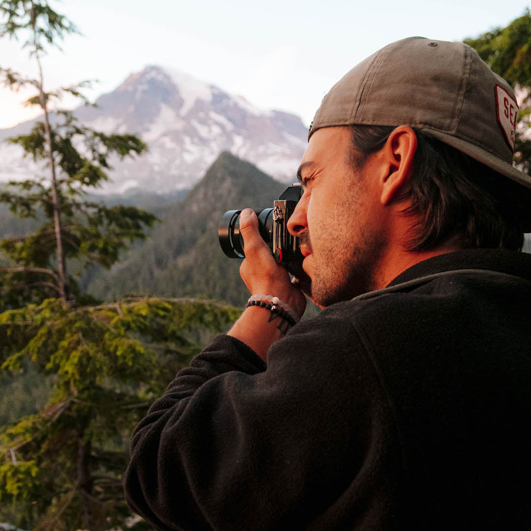 Man taking picture with mountain in the background wearing a black lava stone bracelet on wrist.