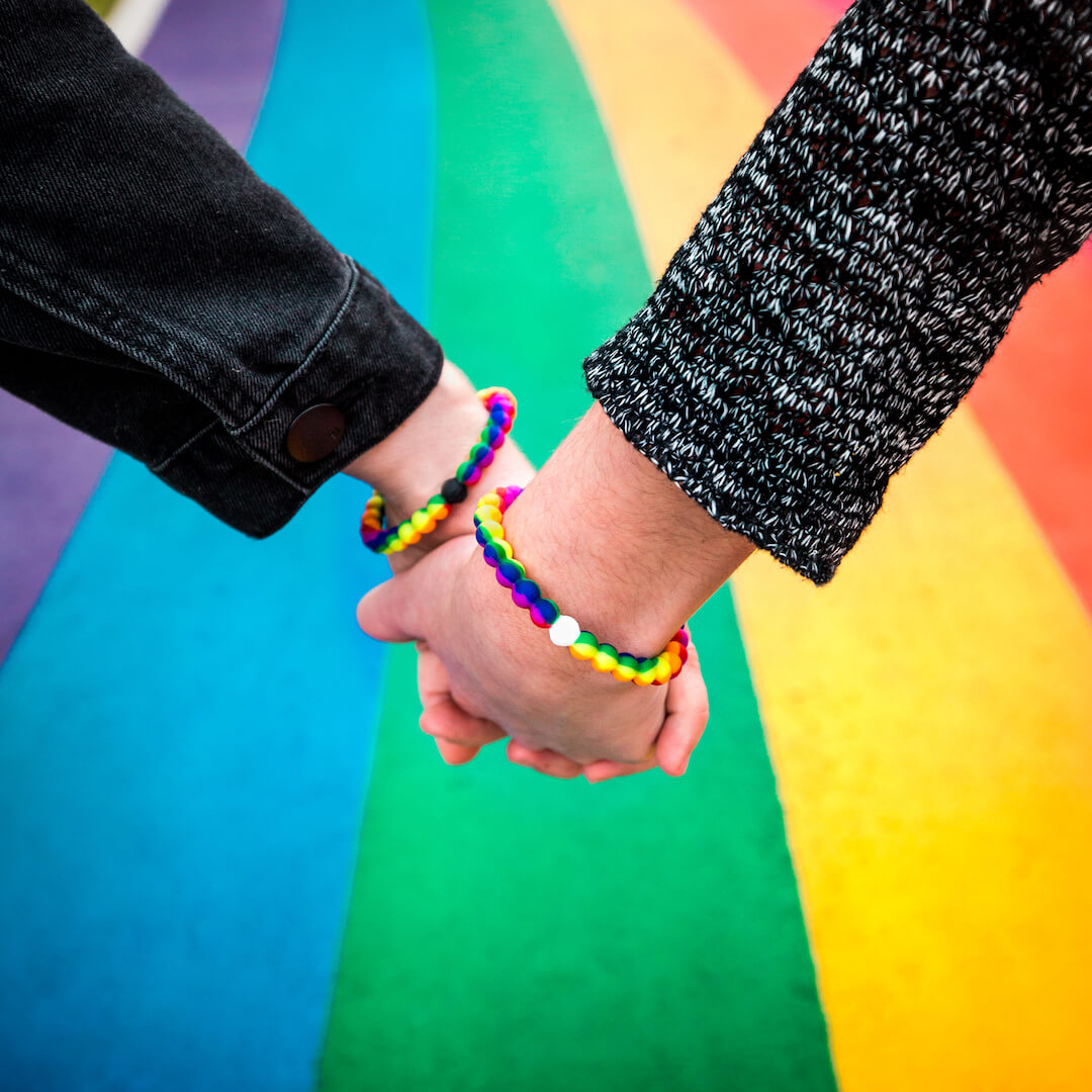 People holding hands with rainbow silicone beaded bracelets on wrist with rainbow sidewalk in the background.
