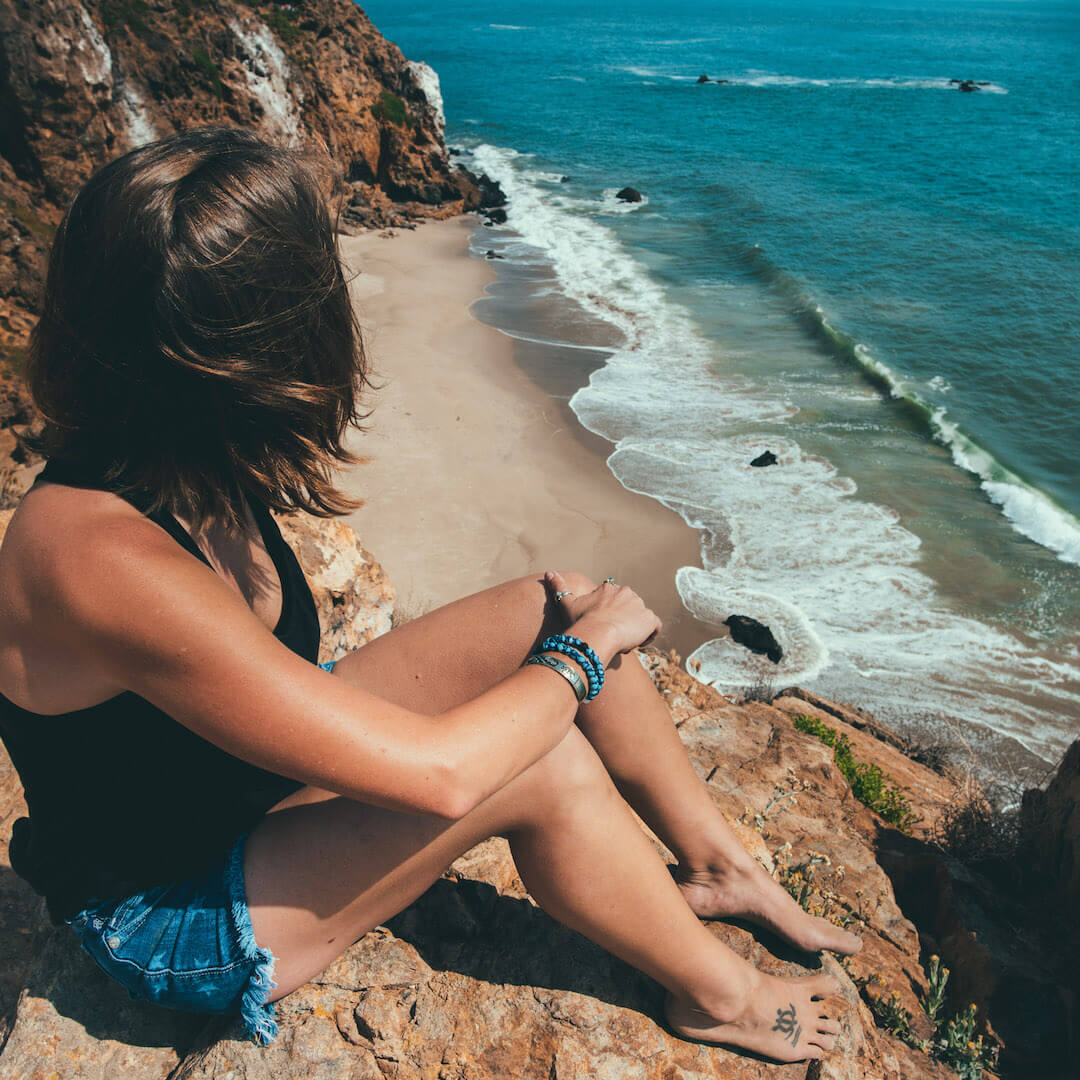 Woman wearing silicone beaded bracelet with wing pattern on wrist sitting on a cliff looking at the ocean.