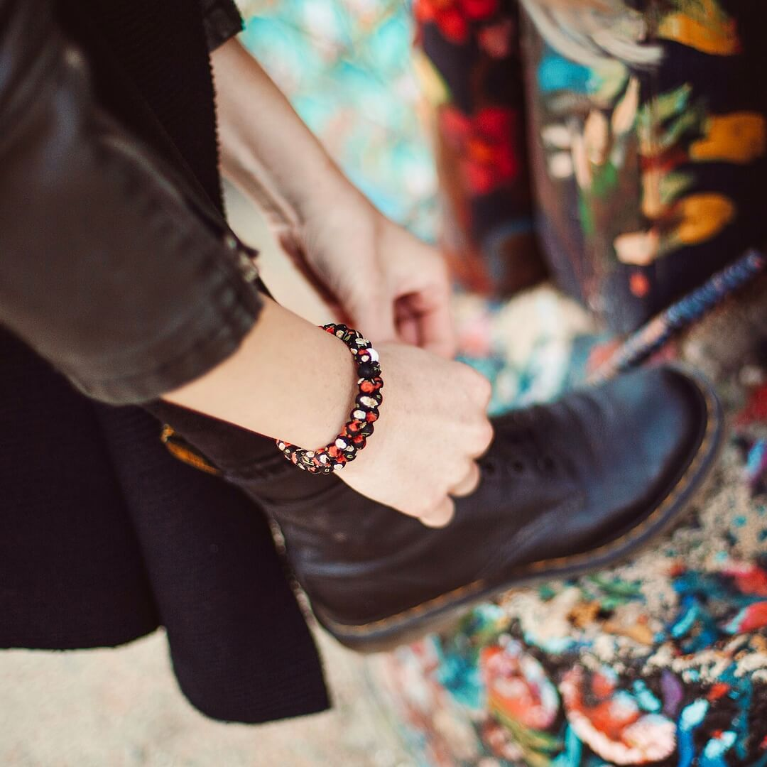 Woman wearing silicone beaded bracelet with rose pattern on wrist while tying boots