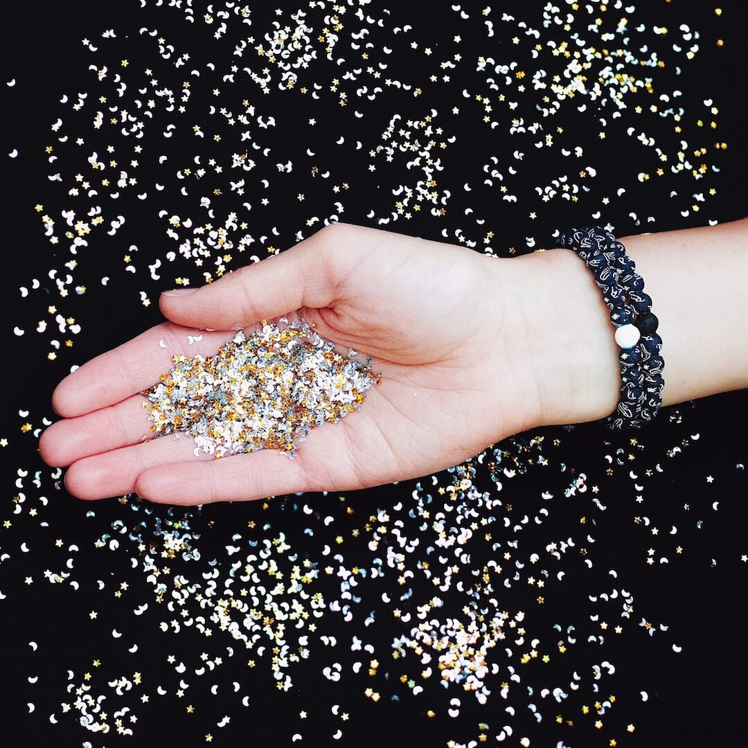 Woman wearing silicone beaded bracelet with glass slipper pattern on wrist while holding glitter