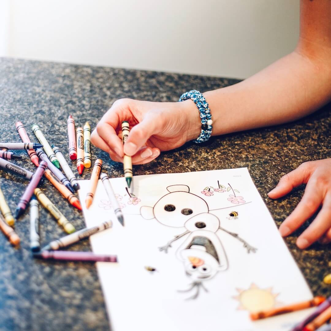 Woman wearing silicone beaded bracelet with Olaf pattern on wrist while drawing Olaf