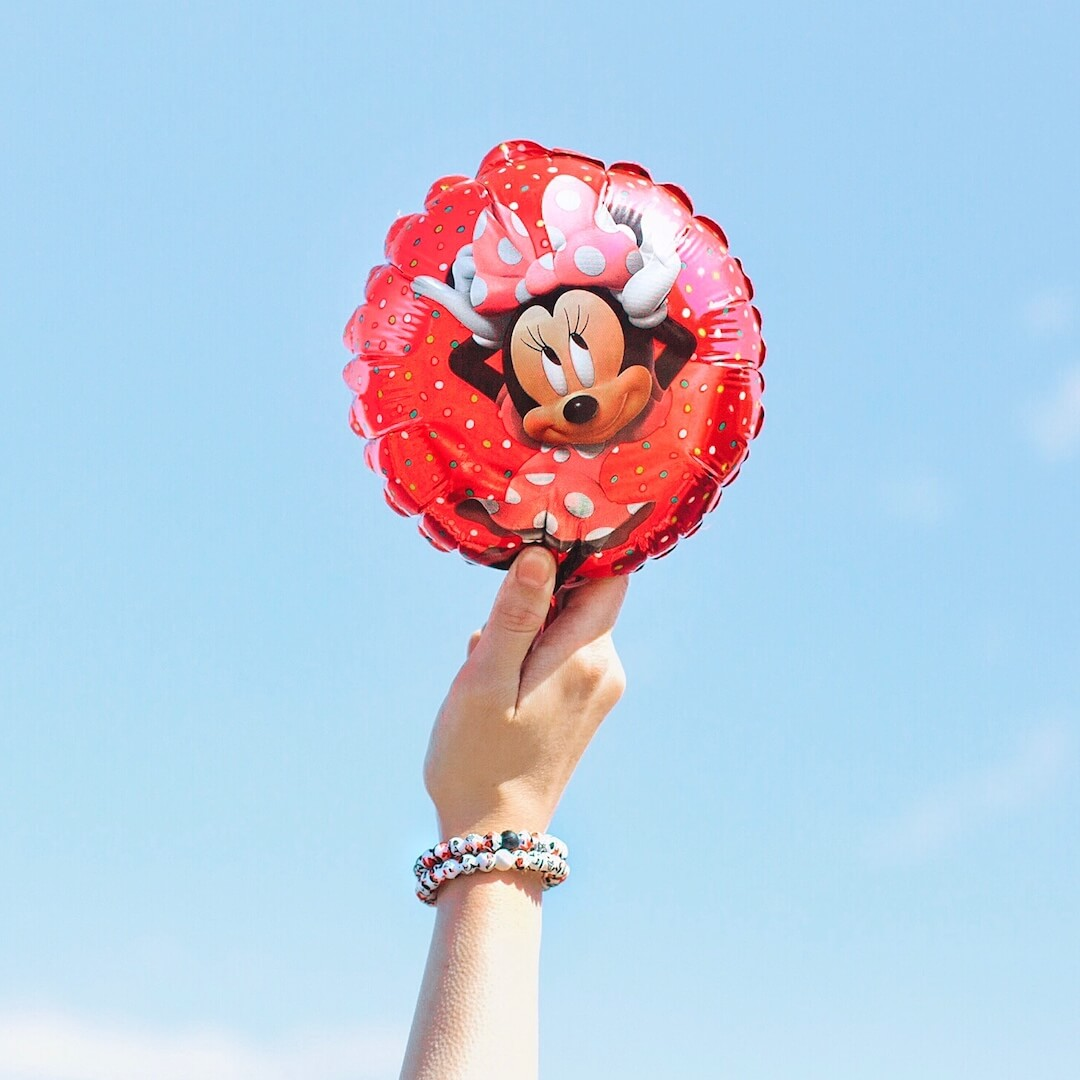 Woman holding Minnie Mouse balloon wearing silicone beaded bracelet with Minnie Mouse pattern on wrist