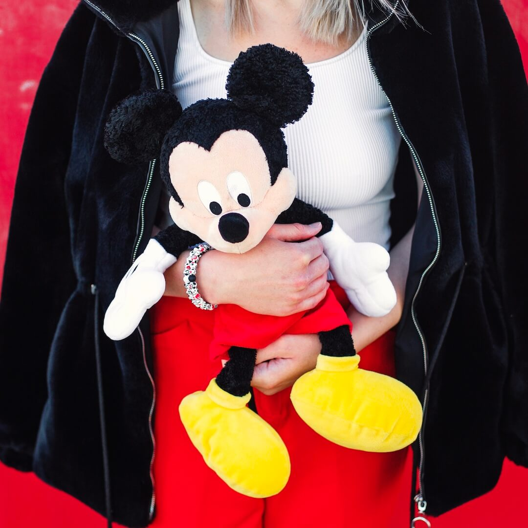 Woman wearing silicone beaded bracelet with Mickey Mouse pattern on wrist while holding Mickey Mouse