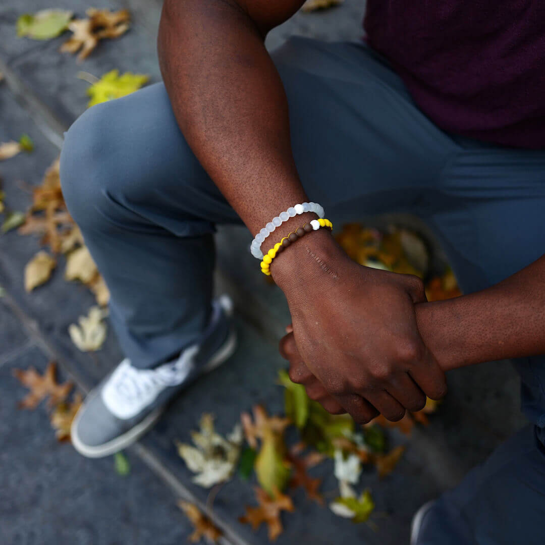 Male wearing yellow and brown silicone beaded bracelet on wrist while seated outside.