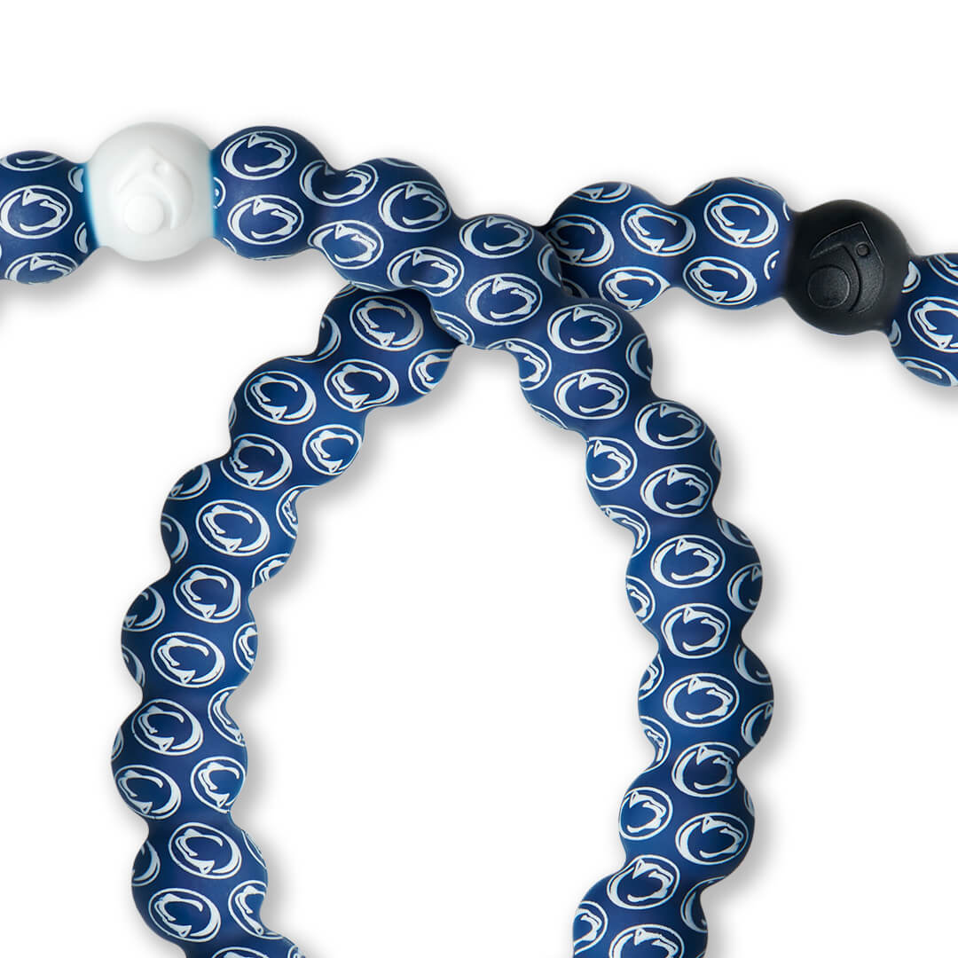 Close-up of white and navy blue silicone beaded bracelet with the Pennsylvania State University logo all over it.