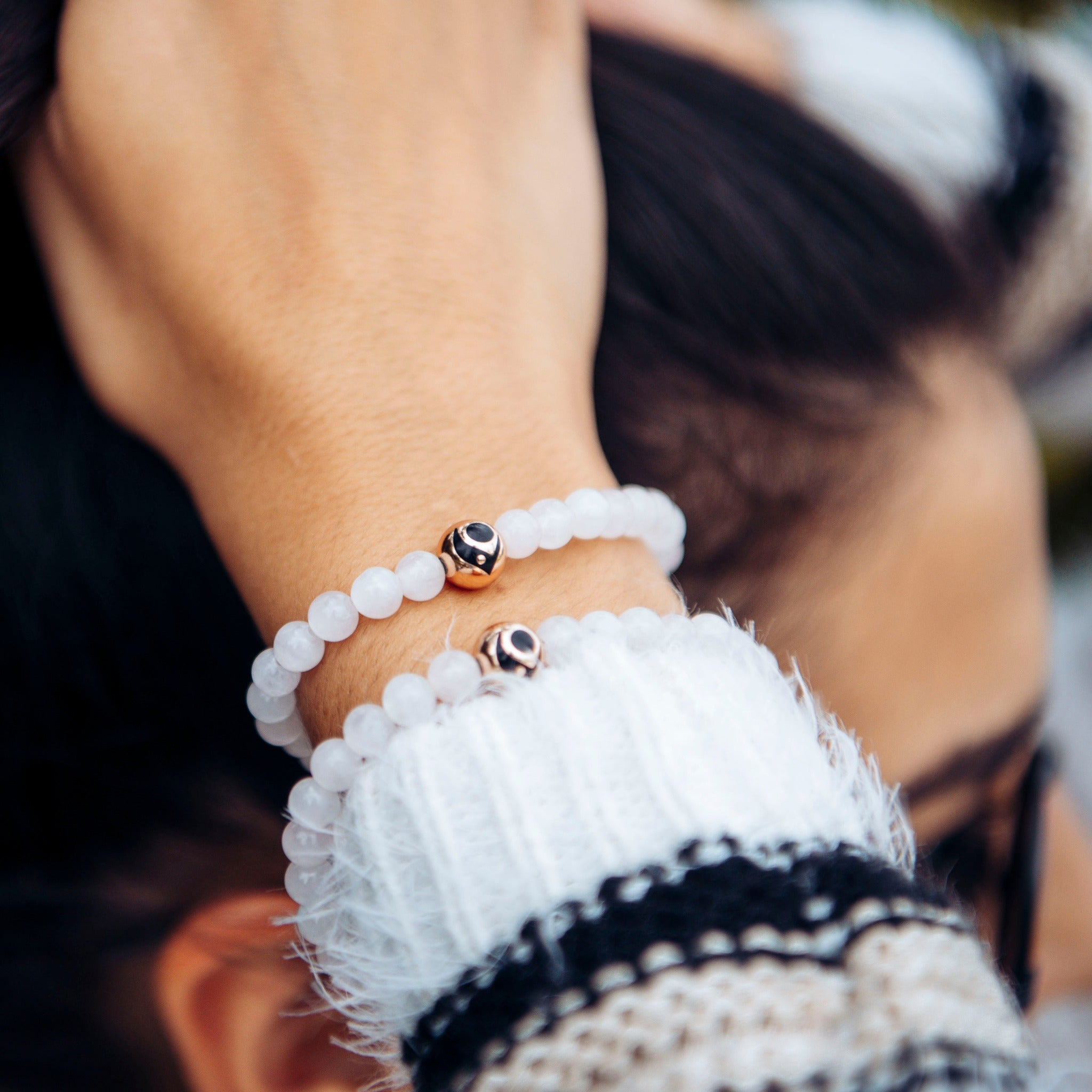 Close up of woman wearing two light pink stone bracelets on wrist while adjusting her ponytail.