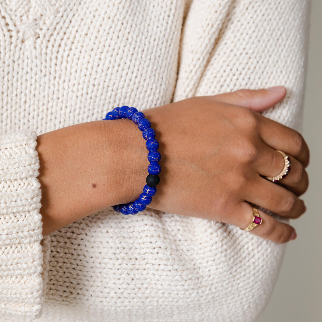 Girl wearing a silicone beaded bracelet with Pisces symbol pattern on wrist.