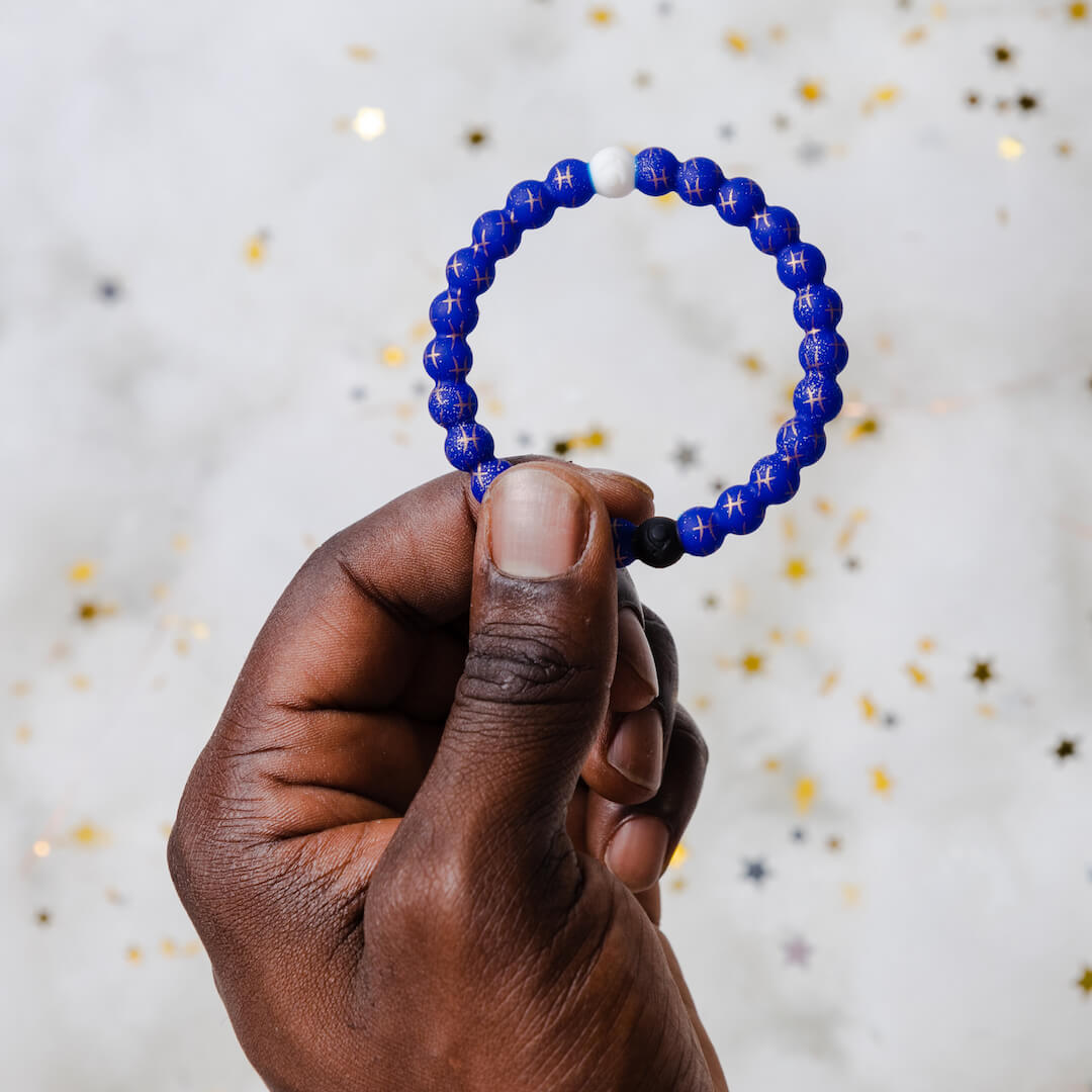 Man holding a silicone beaded bracelet with Pisces symbol pattern.