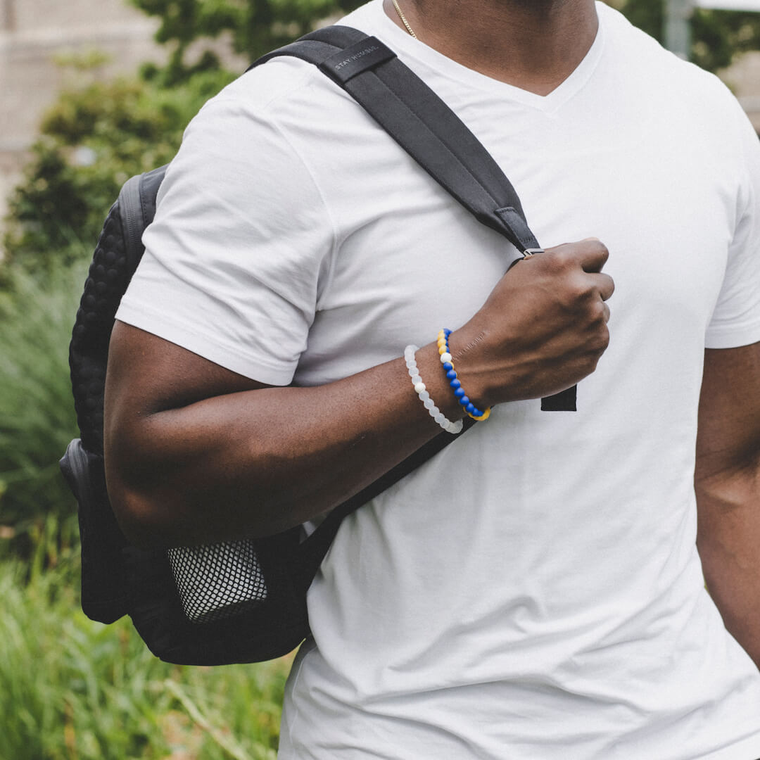 Man holding backpack wearing a blue and yellow silicone beaded bracelet.