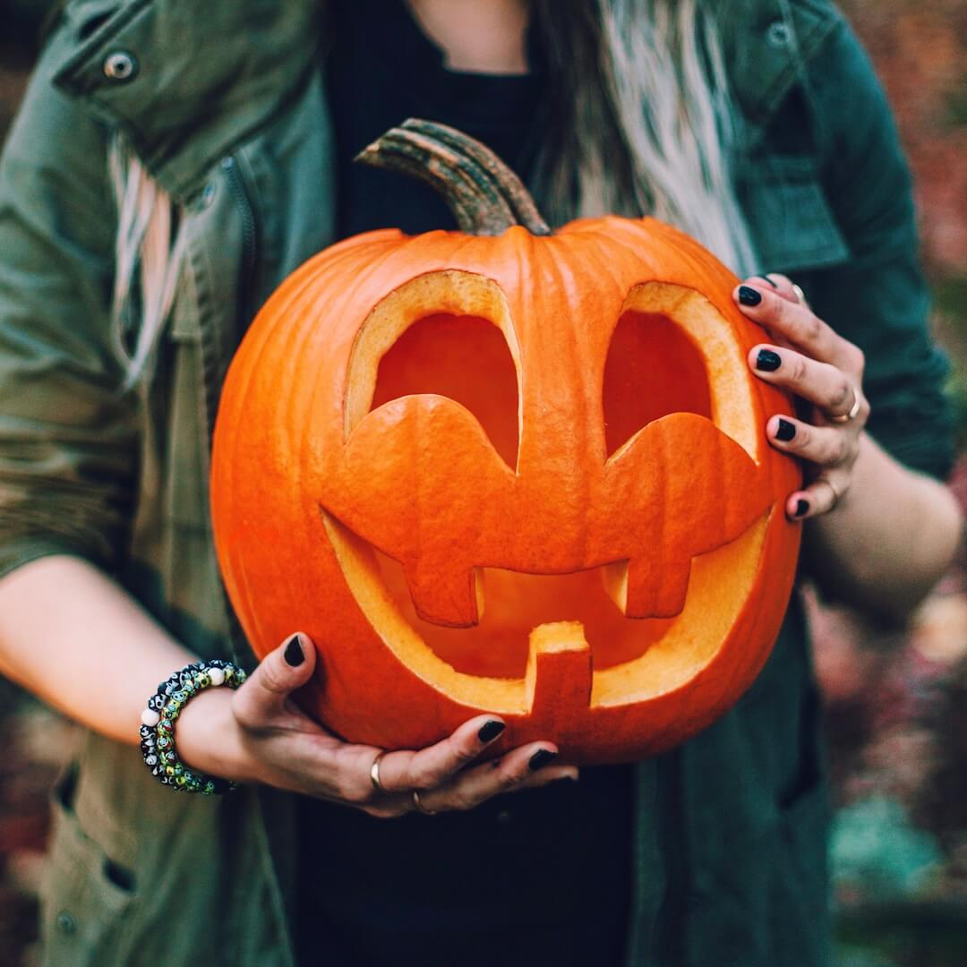 Woman holding pumpkin wearing a silicone beaded bracelet with skeleton pattern