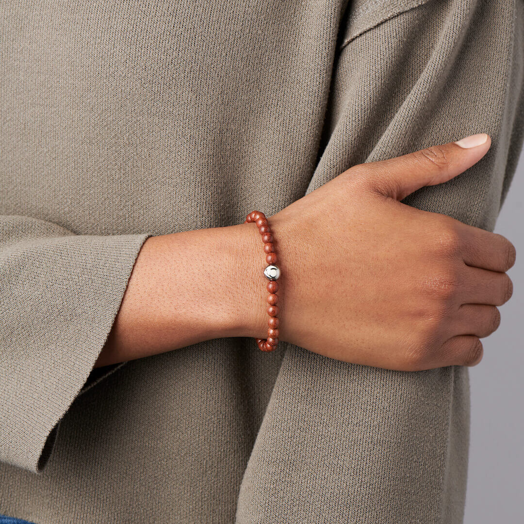 Person wearing red sandalwood beaded bracelet with lokai symbol on either side.