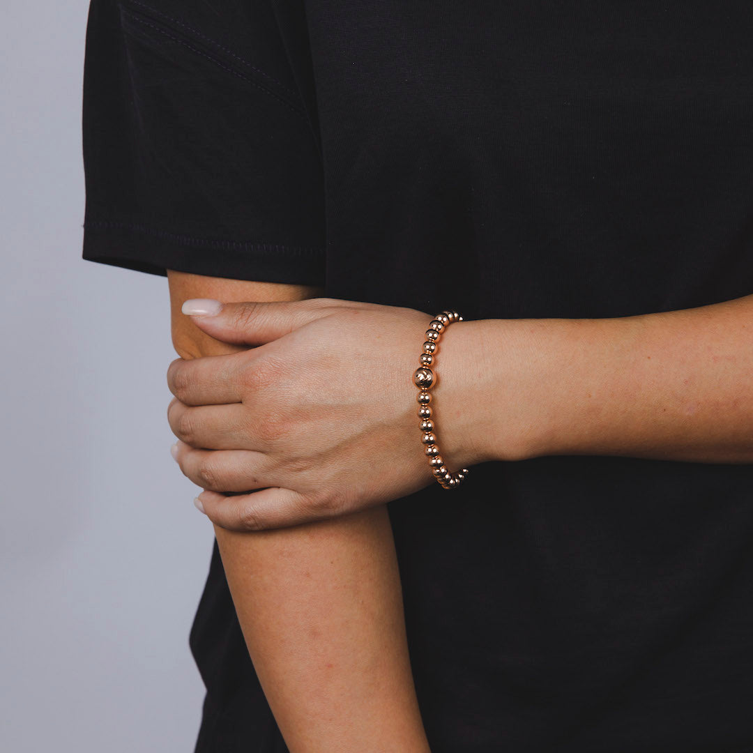 Woman wearing rose gold metal bracelet on wrist.