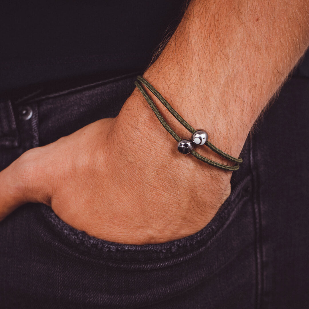 Close up of male wearing light green cord bracelet with two metals beads on wrist with his hand in his pocket.