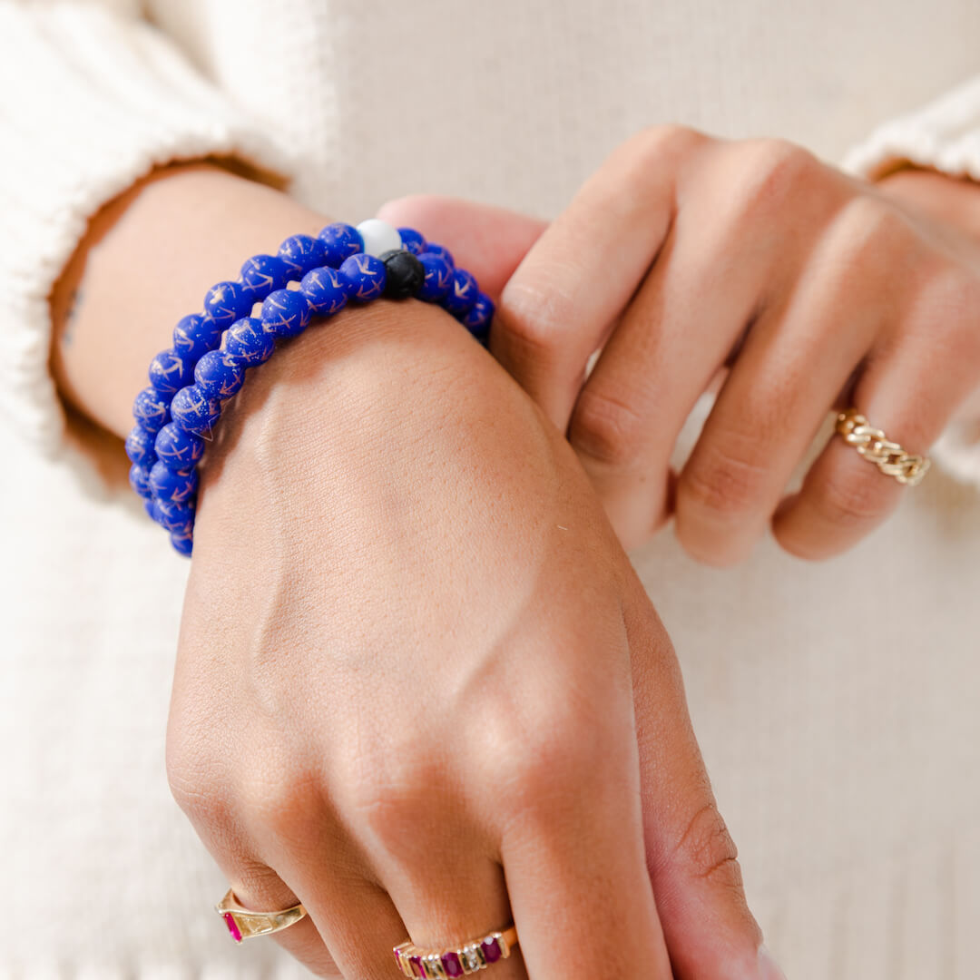 Girl wearing a silicone beaded bracelet with Sagittarius symbol pattern on wrist.