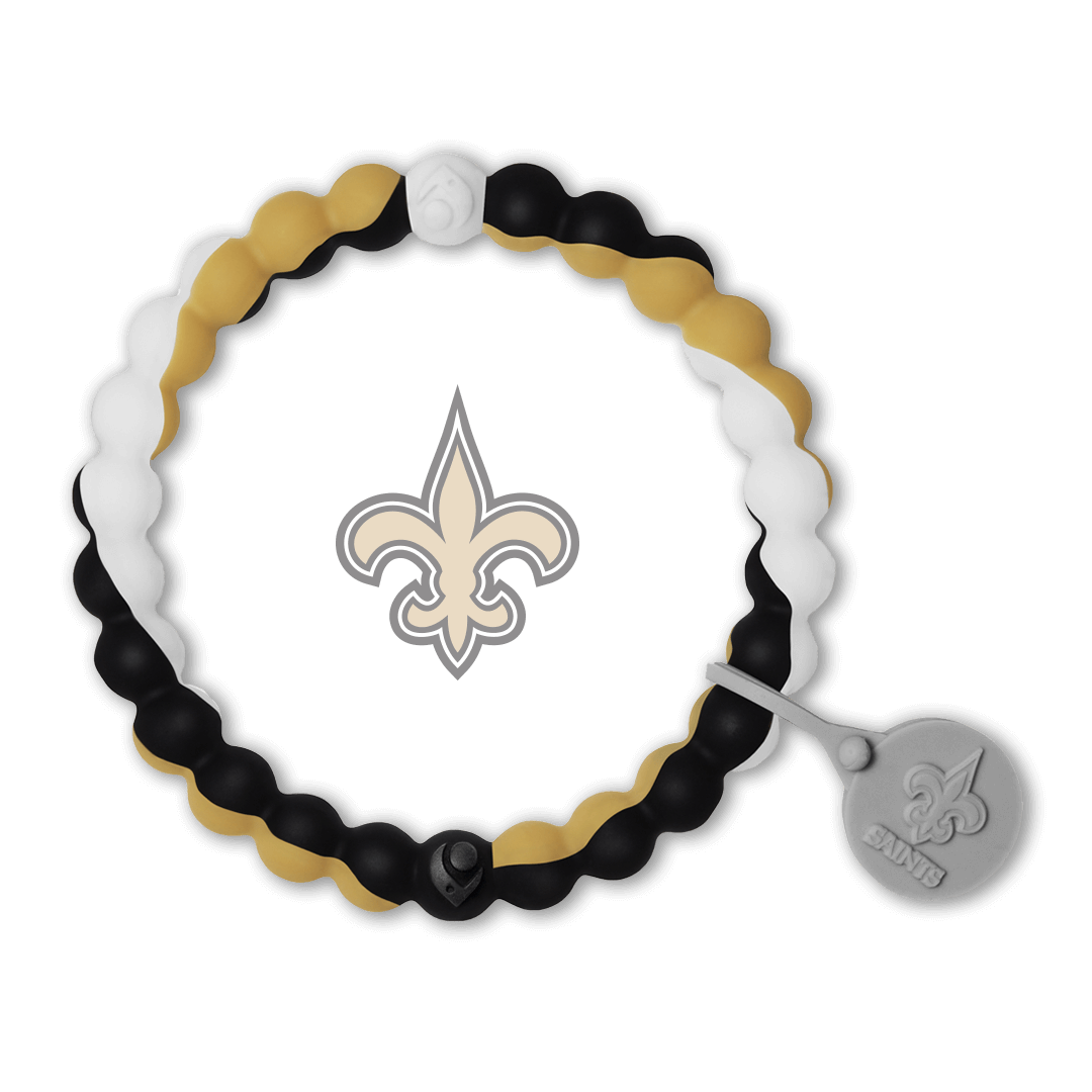 Male wearing a black, gold and white silicone beaded bracelet on wrist while holding a football.