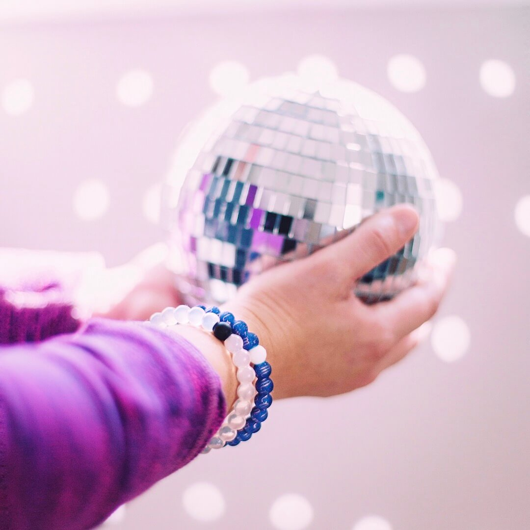Person holding a disco ball wearing a silicone beaded bracelet with Scorpio symbol pattern on wrist.