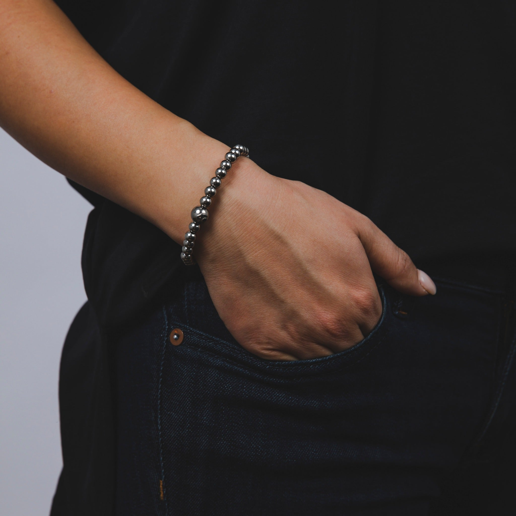 Woman wearing silver metal bead bracelet on wrist.