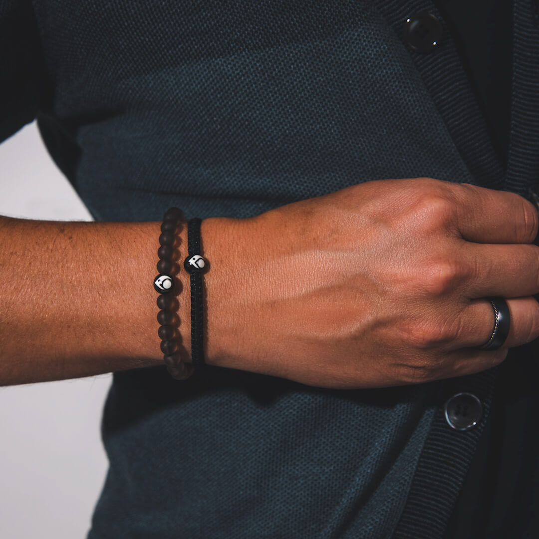 Close up of male wearing transparent smoke glass bead bracelet on wrist while buttoning sweater.