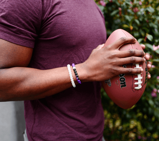 Man holding a football wearing a purple and black silicone beaded bracelet.