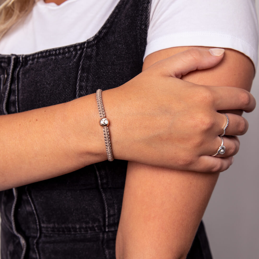 Woman wearing taupe woven bracelet with rose gold metal bead on wrist while holding her other arm.