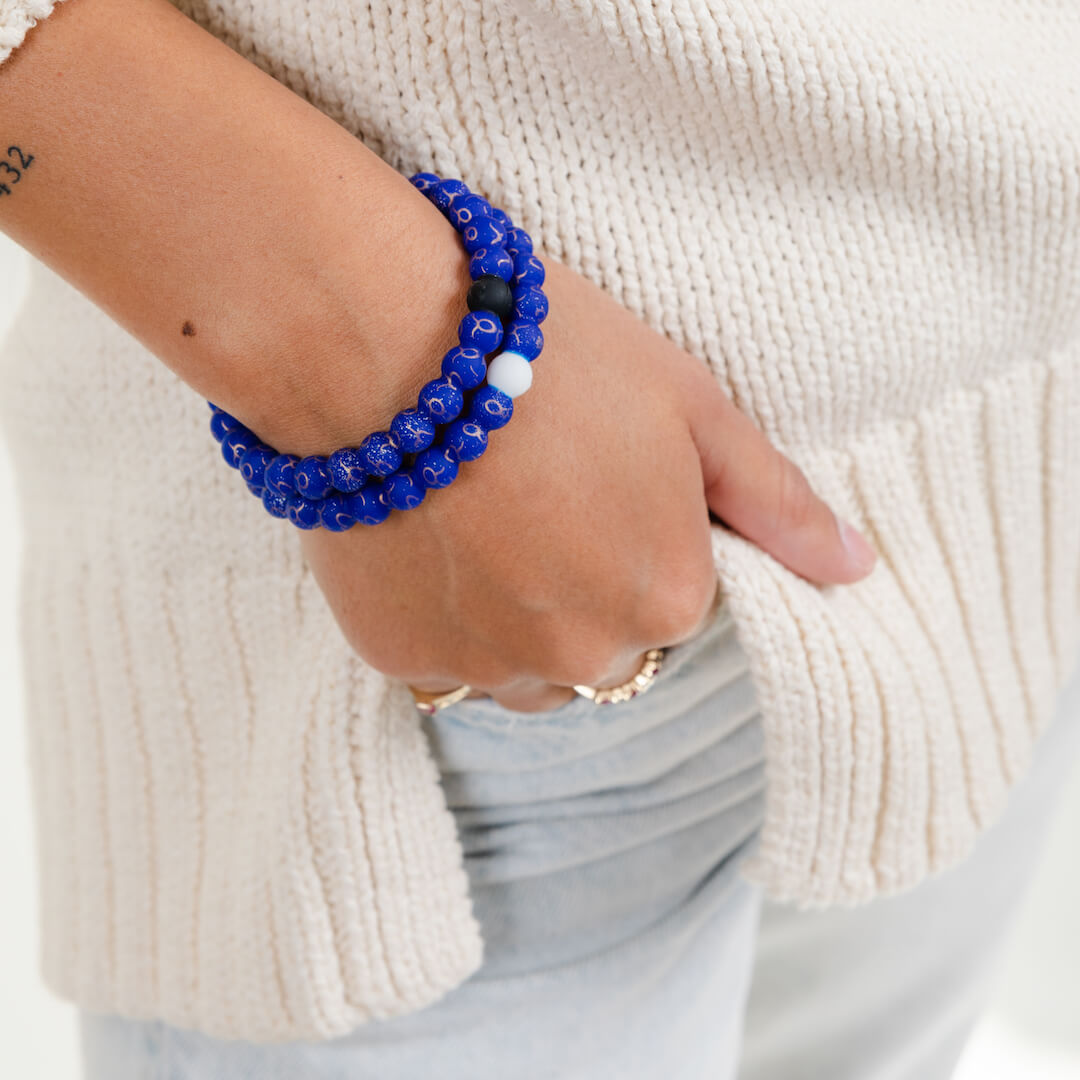 Girl wearing a silicone beaded bracelet with Taurus symbol pattern on wrist.