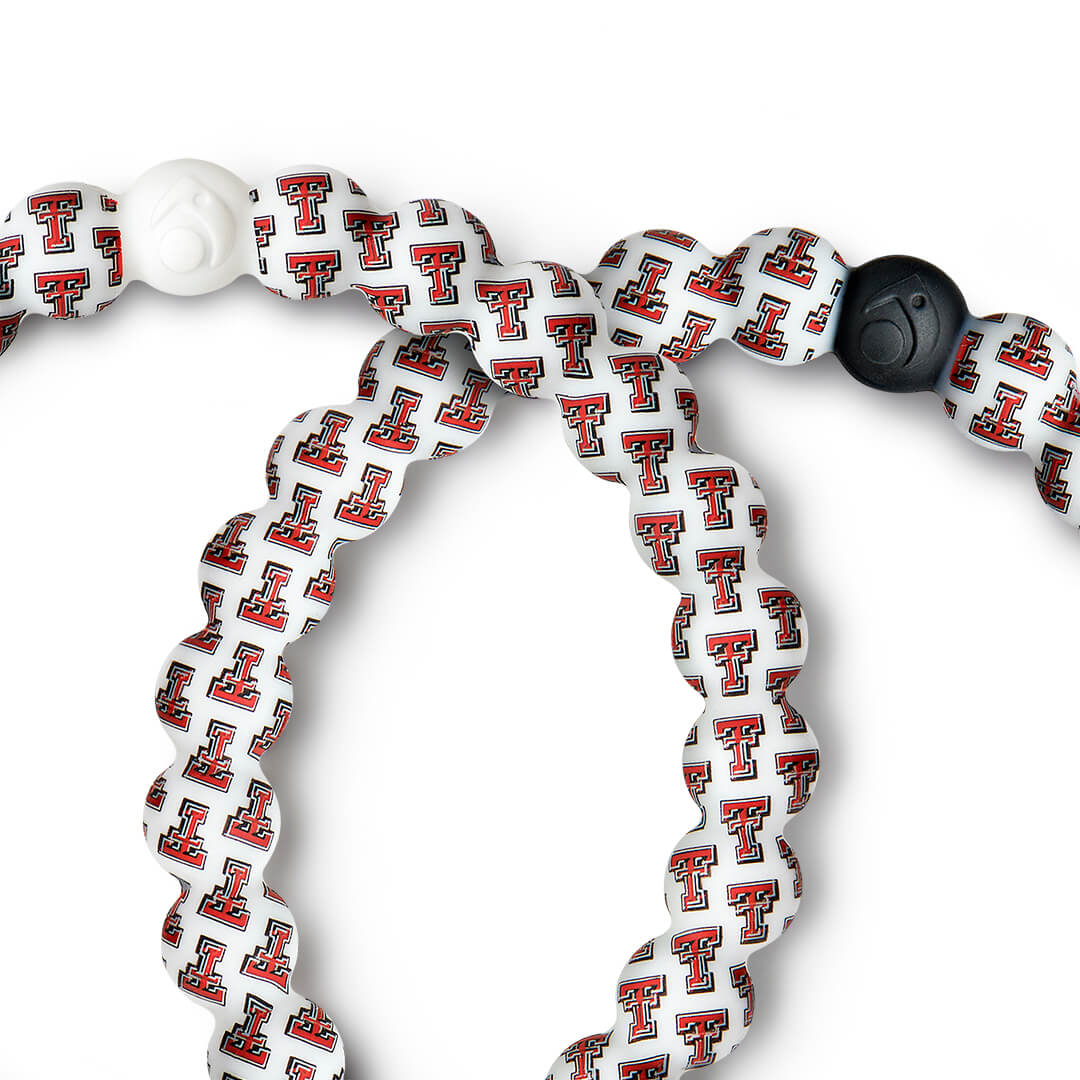 Close-up of a red, white and black silicone beaded bracelet with the Texas Tech University logo all over it.