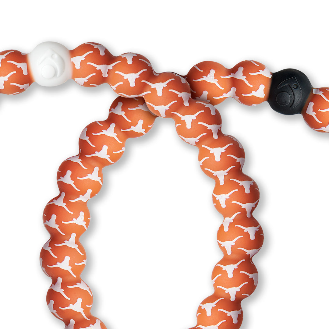 Close-up of orange and white silicone beaded bracelet with the University of Texas logo all over it.