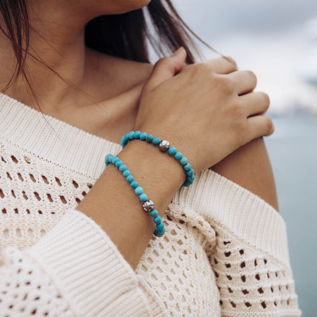 Female wearing two turquoise stone bracelets on wrist while touching her shoulder.