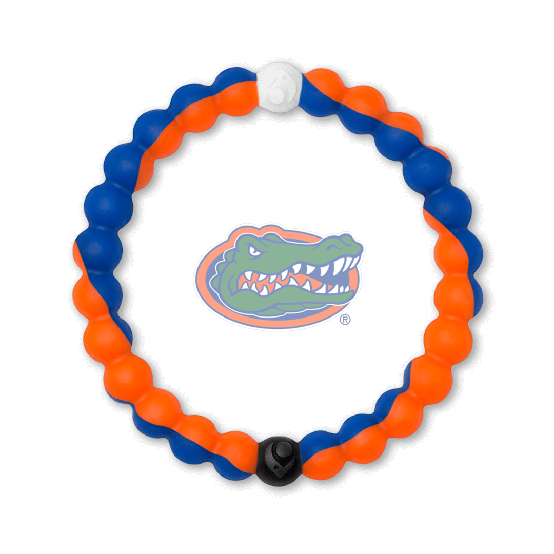 Man holding a football wearing an orange and blue silicone beaded bracelet.