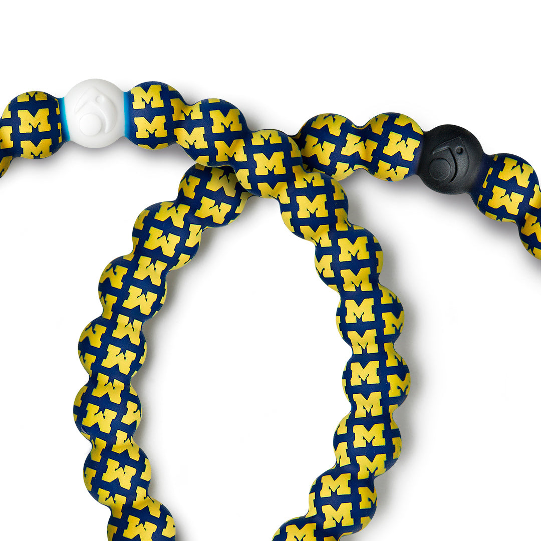 Close-up of Yellow and dark blue silicone beaded bracelet with the University of Michigan pattern on it.