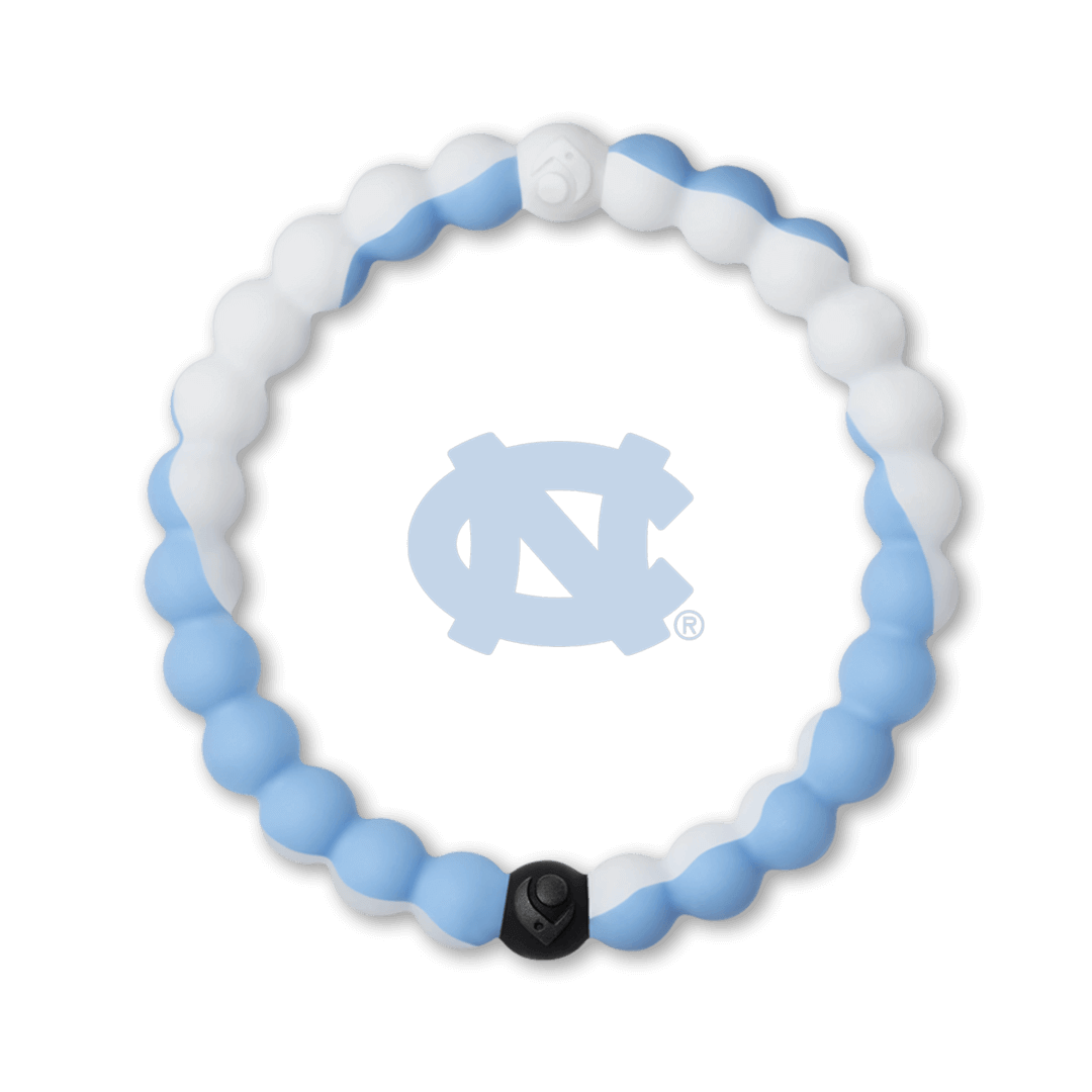 Man holding a football wearing a white and light blue silicone beaded bracelet.