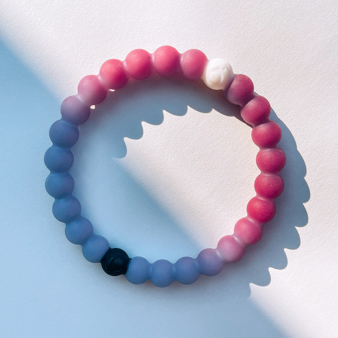 Close-up of a multi-color and navy blue silicone beaded bracelet with the word