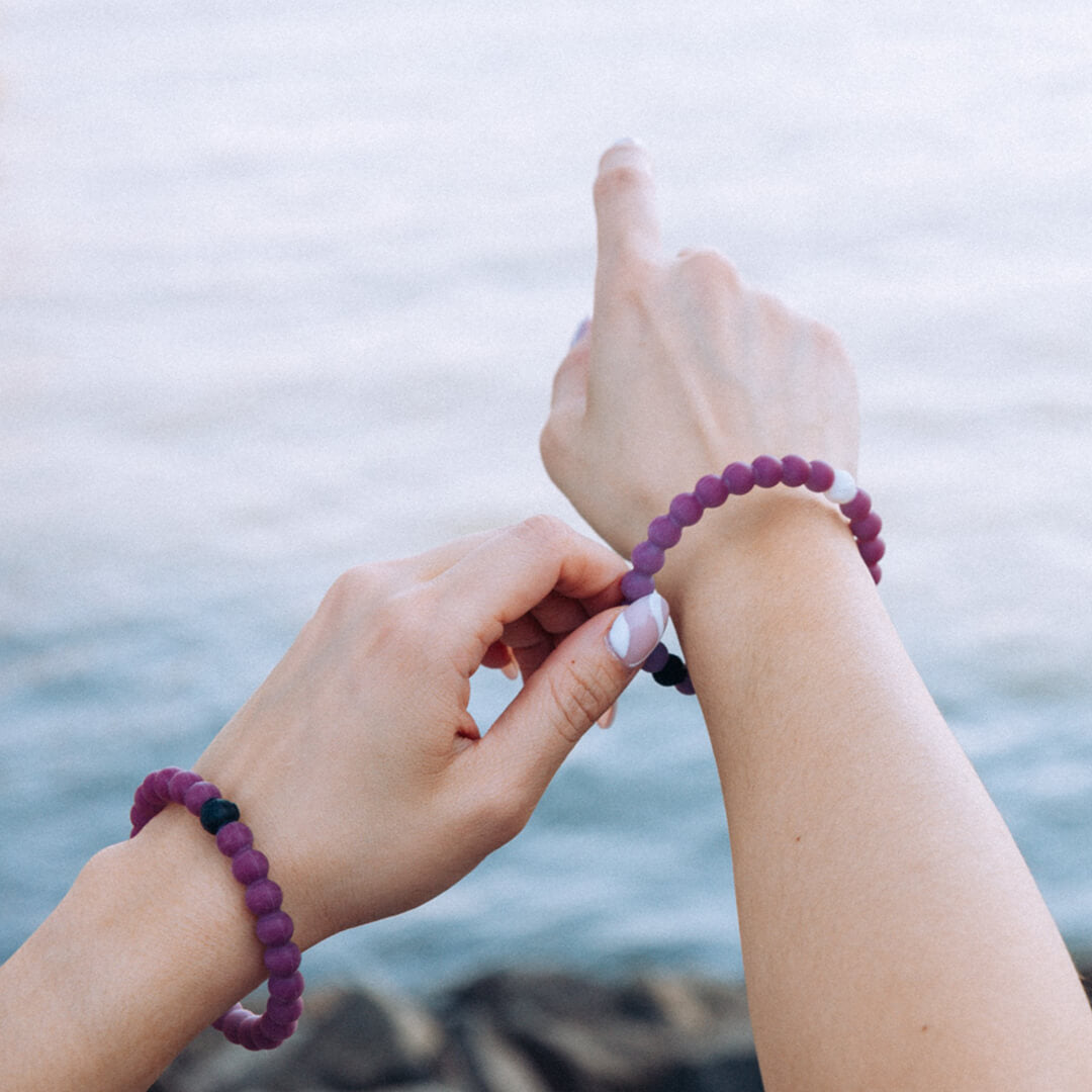 Person wearing a multi-color and navy blue silicone beaded bracelet with the word