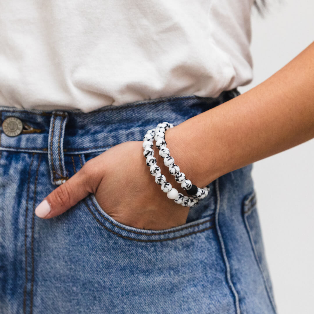 Woman wearing two silicone beaded bracelets with Venom pattern on wrist.